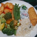 A plate from the buffet filled with garlic green beans, an egg roll, chicken and broccoli, rice noodles and sushi.