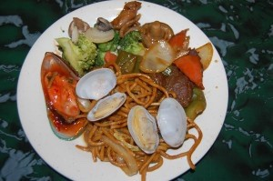 A plate from the buffet with vegetables, clams, and lo mein noodles.