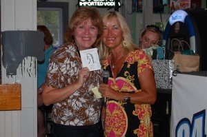 Susan Smith holds her gift certificate for Coastal Carolina Rei-Ta with Irene Goodnight from The Island News.