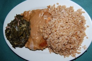 Smothered pork chop with collard greens and shrimp and crab rice.