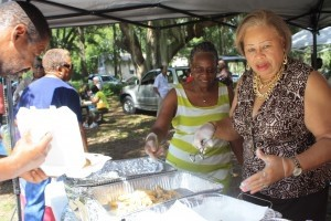 Candidate Joyce Dickerson gets into the spirit of the day by helping to serve fried fish to guests.