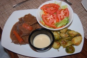 Sauerbraten entree with brussels sprouts and side salad