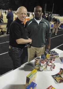 Steve Curless, left, president of HELP of Beaufort, accepts a representation of the more than 7,000-pound donation of nonperishable food from Beaufort High School principal Cory Murphy.