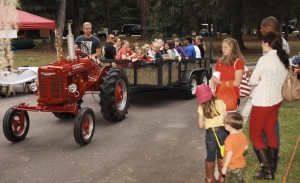 Eric Drugge, left, pulls the hay ride wagon with his vintage 1939 Farm All-A tractor at the Habersham Harvest Festival in 2012.
