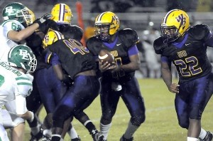 Whale Branch quarterback Amagee Stephens, center, runs the option play as running back DJ Davis, right, moves in during the Warrior's 28-6 win over Bishop England last Friday in Seabrook.