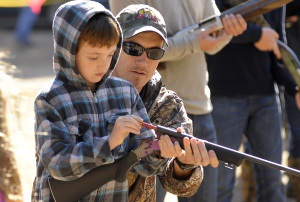 Shooting with the men, 9-year-old Caden Averill takes aim at a paper target 25 yards away. The shooter in the relay with a pellet hole nearest the cross hairs wins a turkey or ham.