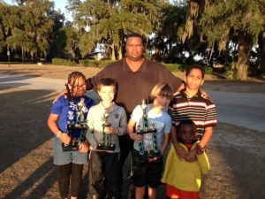 The Beaufort Academy Chess Team participated in two tournaments in the last two weeks.  The first was the Bethesda Academy Chess Tournament on December 6, 2014. In the Elementary Division, BA fourth graders Kendra Rogers and G Simmons placed first and second, respectively. BA fourth grader Jack McDougall participated in his first Middle School Division and placed first, going 5-0. BA sixth grader Kevin Rogers participated in the High School Division. The second was the Golden Isles Scholastic Chess Association Chess Tournament on December 13, 2014. BA second grader Whit Suber finished first in the Primary Division, going undefeated at 5-0. BA fourth graders Kendra Rogers, G Simmons and Jack McDougall placed third as a team in the Elementary Division. BA sixth grader Kevin Rogers once again played in the High School Division. Pictured above, left to right: Kendra Rogers, G Simmons, Coach Darrin Rogers, Jack McDougall, Kevin Rogers, and future BA chess player Kelvin Rogers.