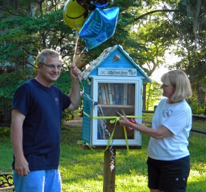 Mark and Terri Stokes at the opening of their Little Free Library exchange stand.