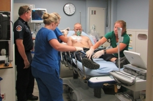 Parris Island EMT Nathan Hildreth delivers a heart attack patient (fellow EMT Charles Bumgardner) to the Beaufort Memorial Emergency Department and updates staff members Christina Crosby, RN, Annalise Kirk, RN and Chelsea Gratton on his condition.
