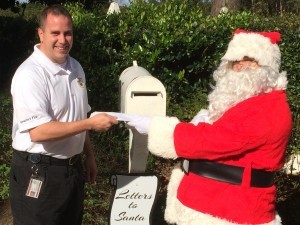 Beaufort Firefighter Joe Lee hands Santa letters from local children as part of a county wide program where Santa mailboxes can be found at every fire station.