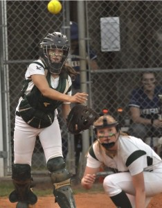 Bricen Riley, left, catcher for the Beaufort High School Lady Eagles, throws the ball to first base after making a play at the plate Monday night against Berkeley High School from Moncks Corner.