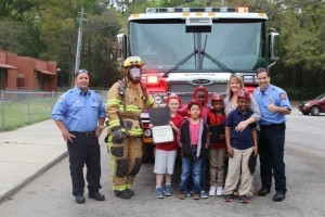 After being presented the awards in front of their peers, and taking their celebratory fire truck ride complete with lights and sirens, the recognized students pose with Burton firefighters and their teacher. From left are Brenden Weber, Reynaldo Alvarado, Kanard Rivers, Kenyatta Major, Tai'jon Best, and teacher Angela Byrne.