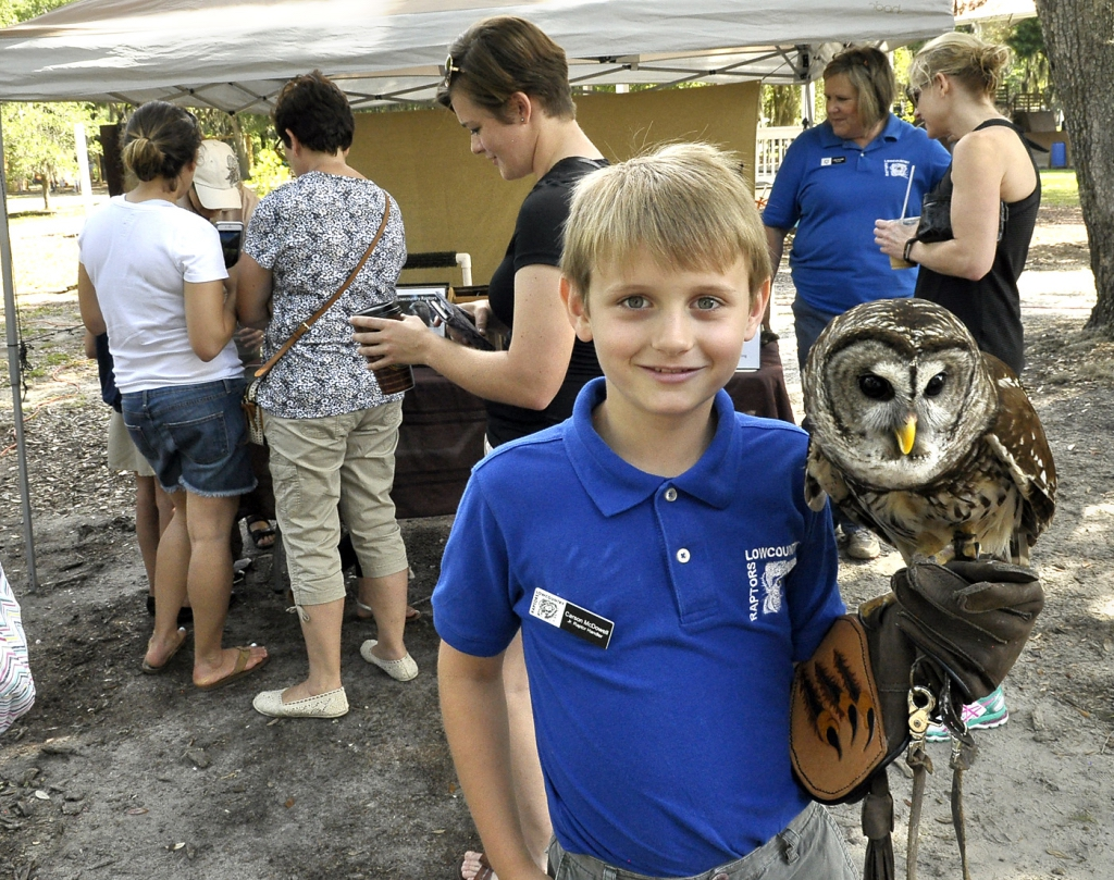 Carson McDowell, a junior raptor handler with the Lowcountry Raptors, holds Breezy, a 2-year-old Barred Owl, during the Port Royal Farmer's Market. The Lowcountry Raptors had several different owls on display.