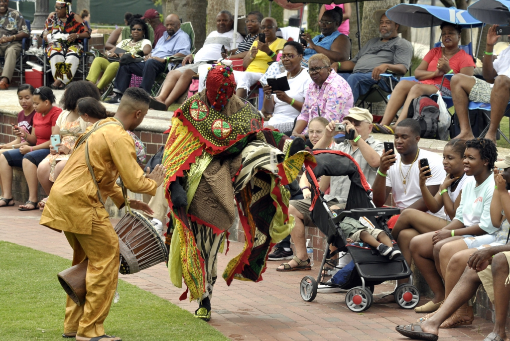 Efunlade Oyewole left, plays the drum while Ere Adetokun dances for the crowd last Saturday during the 30th annual Gullah Festival at Henry C. Chambers Waterfront Park. Oyewole and Adetokun are part of the Oyotungi Yoruba African Drummers from Sheldon. Photos by Bob Sofaly.