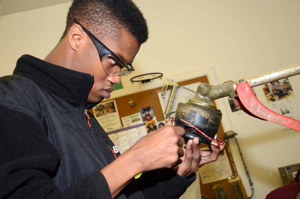 Hakeem Green works on a small engine in an Applied Academics class.