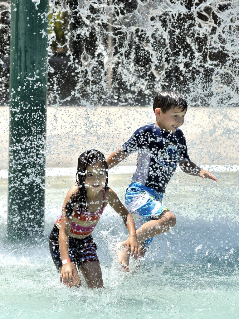 Roberto Sanchez, 6, right, jumps through the water fountain just ahead of Helen Mongo, 7.
