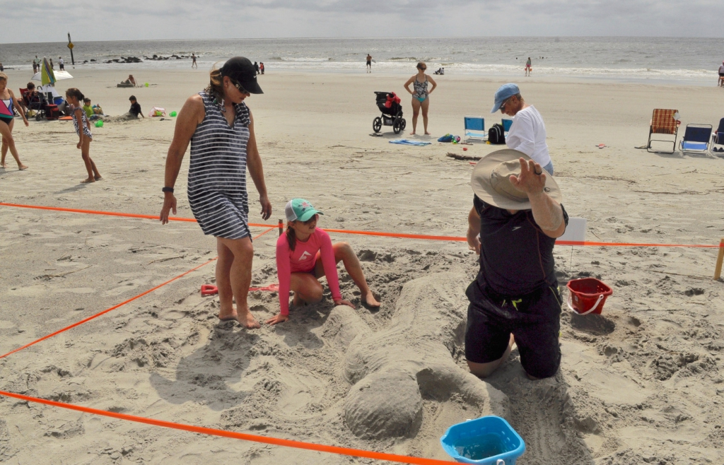 Patrick O'Donnell, right, from Lexington, Ky., shows his daughter, Caroline, and wife Allie, far left, how their swimmer sand sculpture should look.