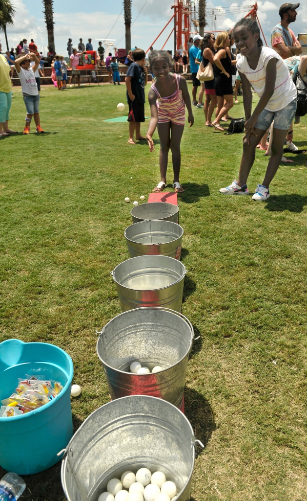 These girls had a difficult time getting a ping pong ball to land in a bucket to get as prize at Children's Day at the Water Fest. The pair finally made the bucket, got a prize and moved on to another game.