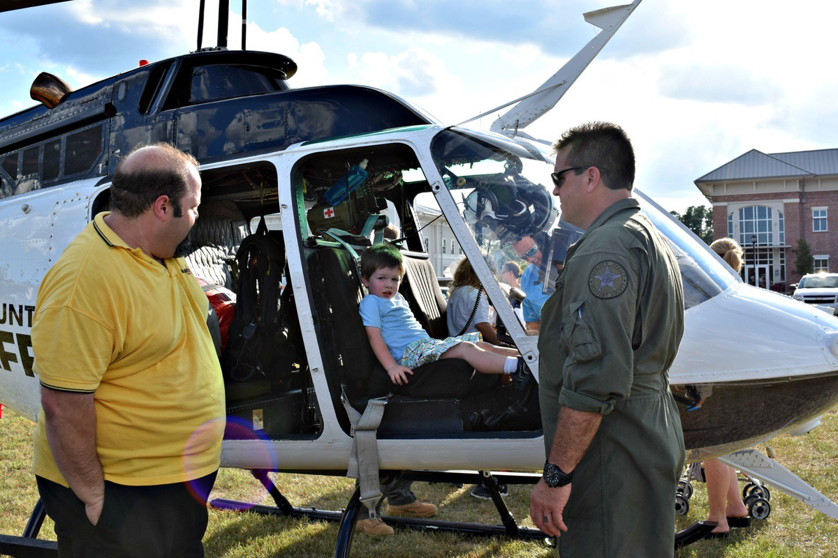 Luke Guzman, 3, sits in the Beaufort County Sheriff's Office helicopter under the watchful eye of his father. Photo by Aileen Goldstein.