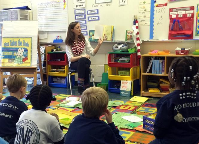 An early care and education student reads aloud to children at a local elementary school.