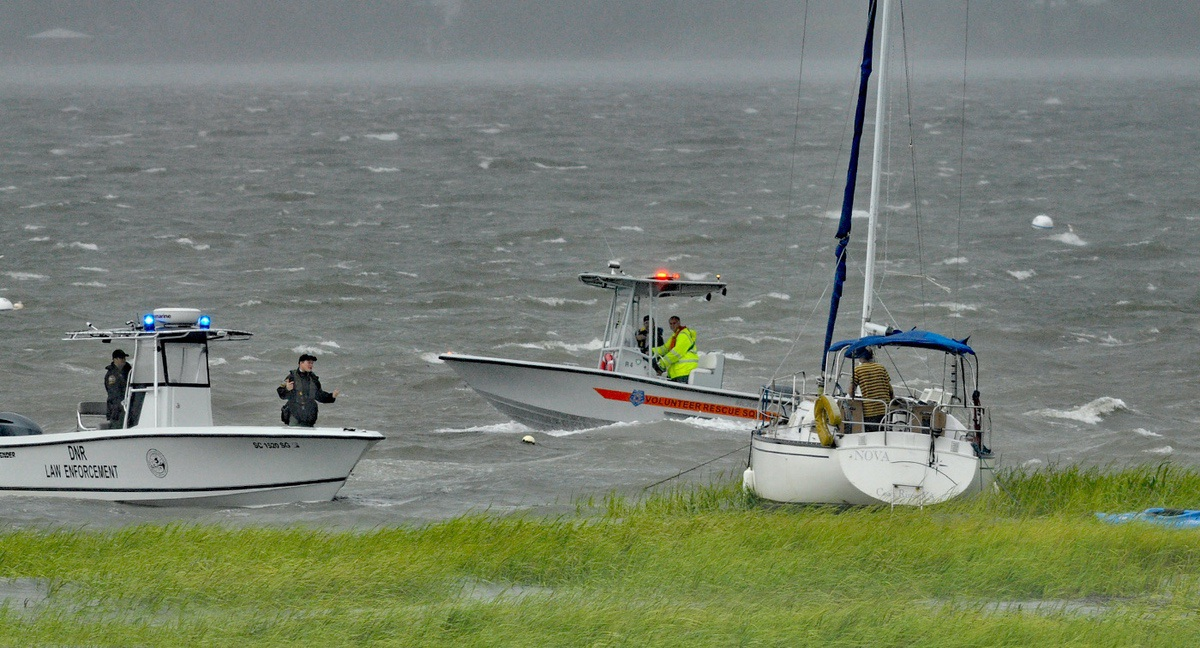 Officers with the S.C. Department of Natural Resources, left, and volunteers with the Volunteer Rescue Squad try to convince a man to get off his boat after it broke loose and drifted into the marsh near the Downtown Beaufort Marina on Sept. 2 as Hermine made its way up the South Carolina coast. Photo by Bob Sofaly.