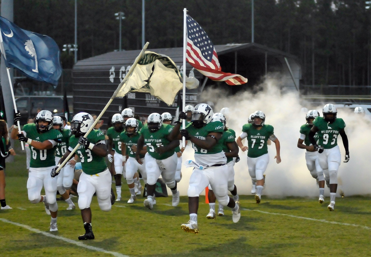 Leading the charge onto their home field, Bluffton High School's Tyrone Mitchell, center, carries the Stars and Stripes. Photo by Bob Sofaly.