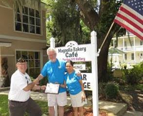 American Legion Beaufort Post 9 is striving to promote both patriotism and businesses in the Beaufort area by calling attention to those that proudly display the U.S. flag at their location. Post 9 presents those enterprises with a framed certificate thanking them. Here, Dana and Jing Johnsrude of Magnolia Bakery accept a certificate from Post Commander Chuck Lurey.