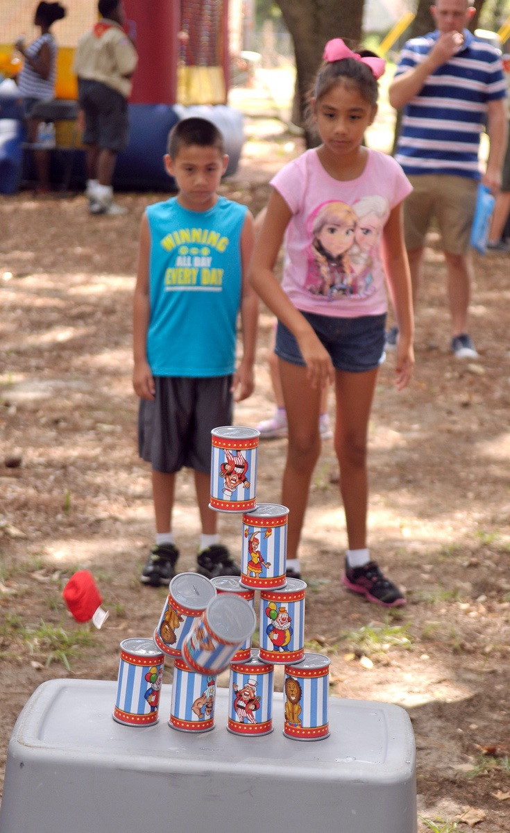 Janelle Rodriguez, 9, right, knocks down the pyramid of cans to win a prize during Military Appreciation Day. Janelle's dad is a drill instructor at Marine Corps Recruit Depot Parris Island.