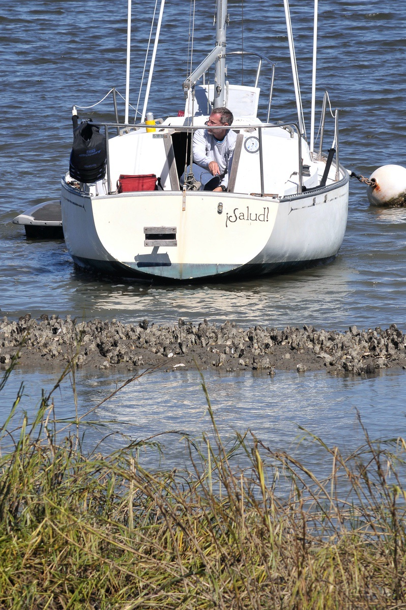An unidentified man bails water from his sailboat that nearly ran aground in Factory Creek. Photo by Bob Sofaly.