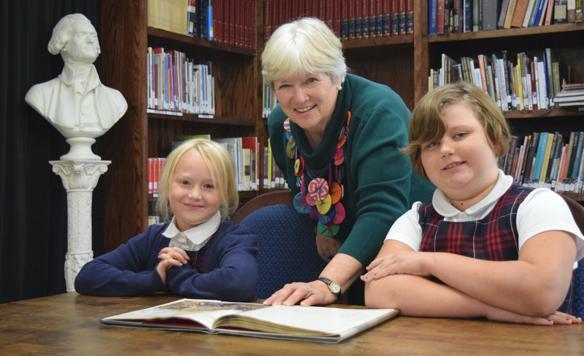 Librarian Barbara Hathaway reads a Shakespearean play with Holy Trinity third-graders Cady O'Connell and Molleigh Reaves.