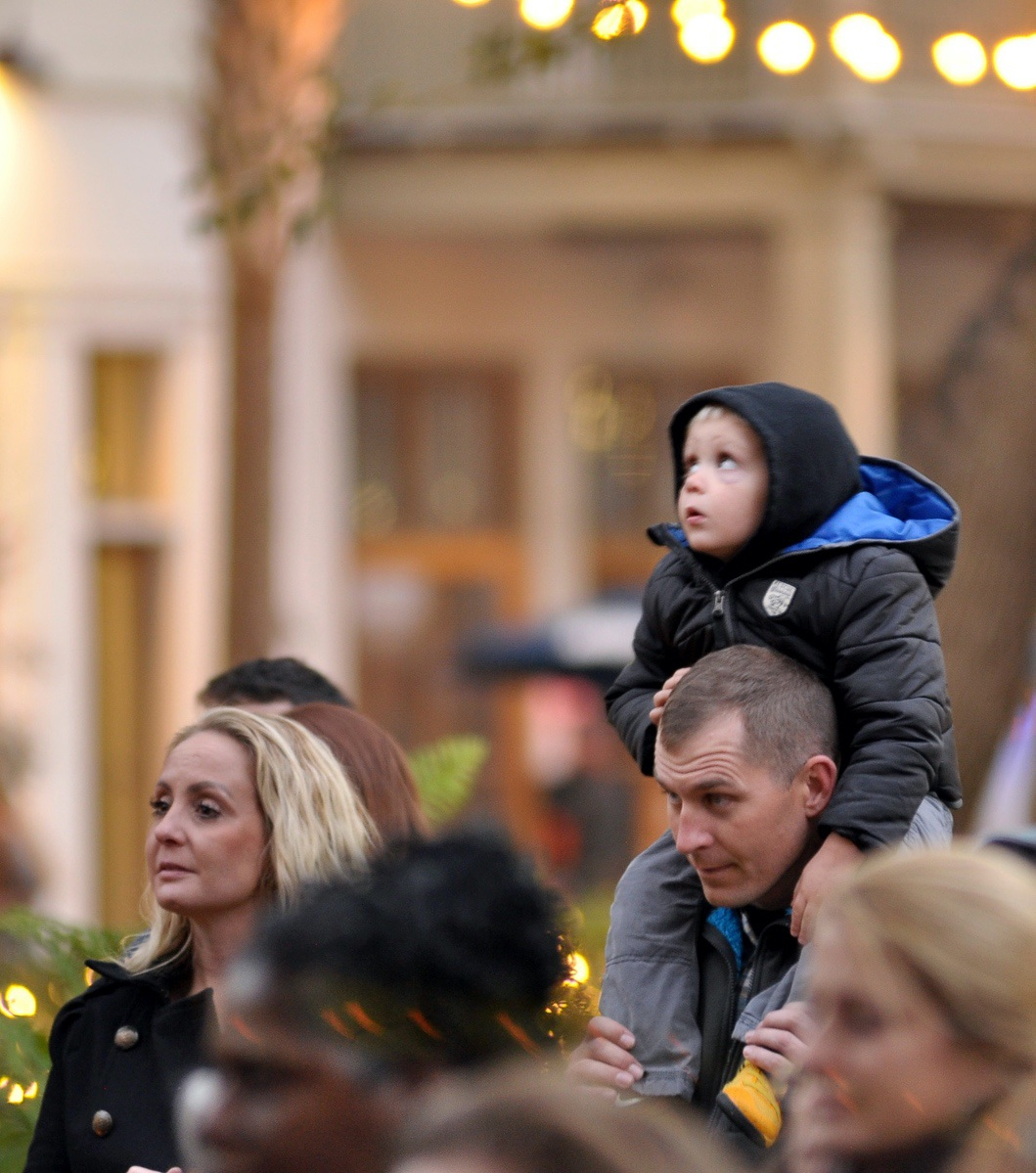 A boy looks up at the lights while sitting on his father's shoulders during the Light Up the Night Family Festival.