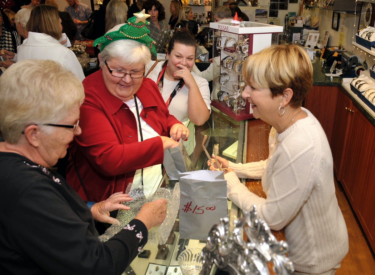 Rosemary Cupia, right, co-owner of Modern Jewelers helps guests with their gifts.