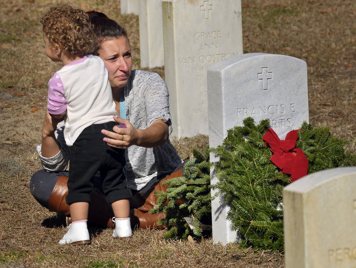 Johanna Roberts holds her 19-month-old daughter Marleigh Beam during the Wreaths Across America at Beaufort National Cemetery.