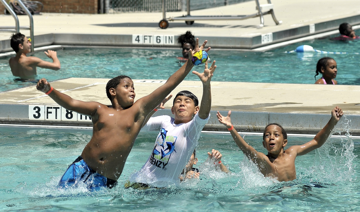 "Three boys have some fun with a ball during the summer in the pool of Charles ""Lynd"" Brown Community Activity Center."