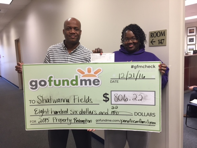 PAFEN First Vice Chair Stephen A. MaHayle, of Jamaica, left, presents an $806.22 gofundme check to Grays Hill resident Shatwanna Fields to redeem her mobile home lot, which was sold at the 2015 Beaufort County Delinquent Tax Sale. A guaranteed funds payment was submitted to the Beaufort County Treasurer's Office on Fields' behalf. Fields was among the Gullah-Geechee families who received more than $10,000 in property tax assistance from the PAFEN in 2016.