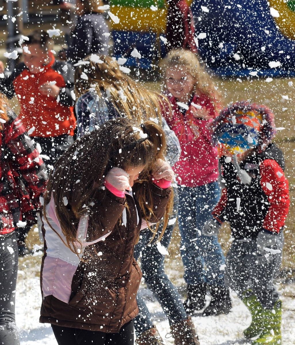 Children shield themselves from falling snow during Snow Day at Red Dam Baptist Church in Hardeeville.