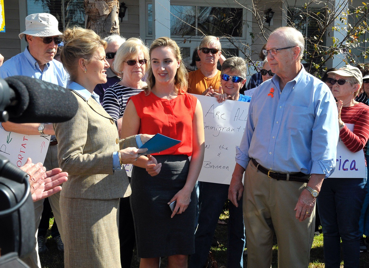 Special Representative Cris Steele, left, and Field Representative Sarah Kimball, center, of Rep. Mark Sanford's office, accept a letter from George Kanuck during a rally regarding immigration.