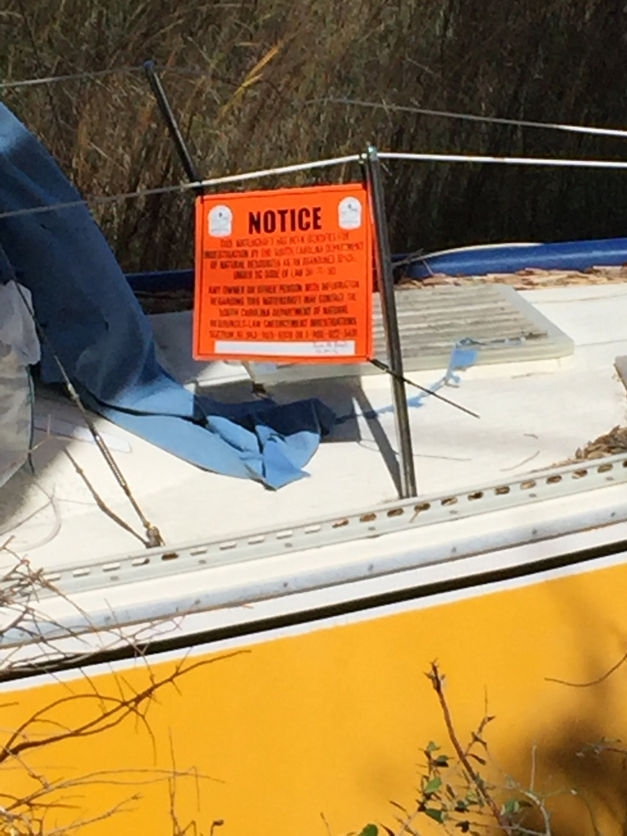 Abandoned boats have an orange sign posted by the South Carolina Department of Natural Resources asking for information regarding the owners of the vessels. The phone number is 800-922-5431.