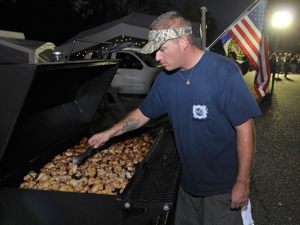 """Allen Kincheloe off the Ashley River Fire Department's """"River Rats"""" BBA team, turns the chicken wings during the annual Bands, Brews & BBQ."""