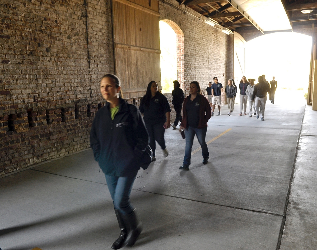 Students, teachers and administrators walked part of the Spanish Moss Trail recently. Here, the make their way through the old rail loading station along the trail.