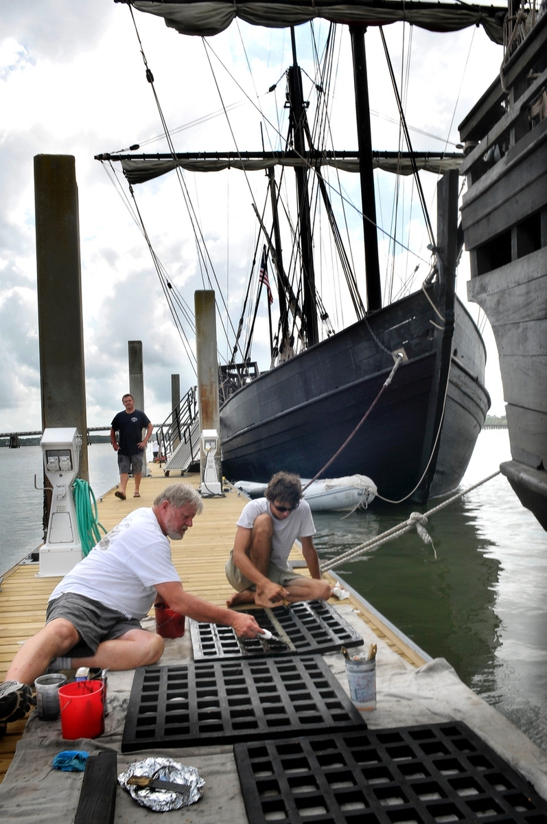 Crewmen add stain to the deck hatches. One crew member said there is always something to do aboard the replicas of Christopher Columbus' ships.