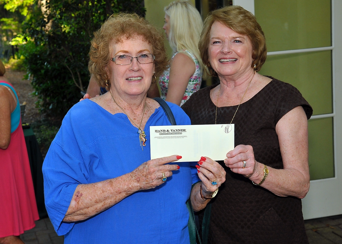 Martha Ala, left, won a gift certificate from Hand & Tanner's Gail Greenway.