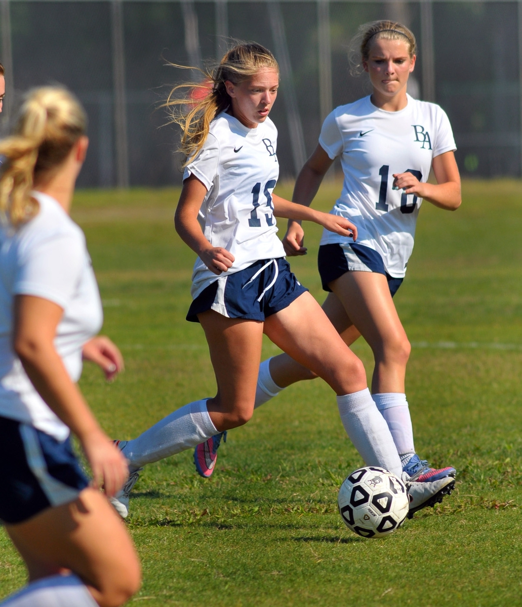 Beaufort Academy's Ally Raschella, center, gets ready to pass the ball  tip field during the first half of the first round of SCISA Girls Class A playoff game at Merritt Field. Assisting Raschella at right is Mary Alden Cooper. Photo by Bob Sofaly.