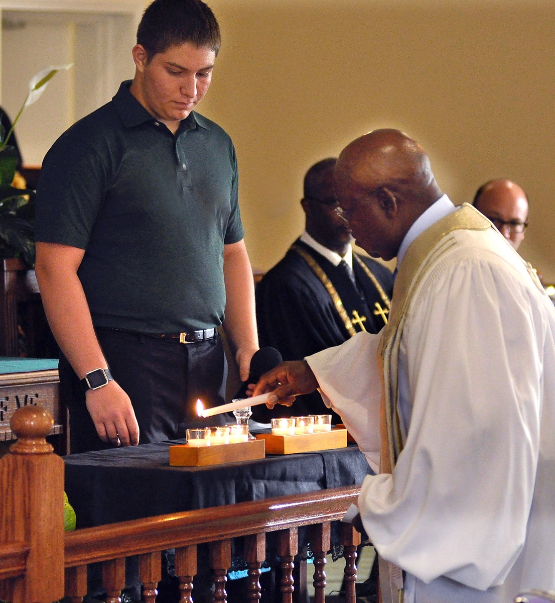 """The Rev. Arthur Cummings, right, president of the Beaufort County Ministerial Alliance, lights the last candle on June 16 in memory of the """"Emanuel Nine"""" who were murdered two years ago while attending Emanuel AME Church in Charleston. The candles were part of the Evening of Remembrance Memorial Candlelight Service sponsored by the Unified Interfaith Community Coalition of Beaufort at Grace Chapel AME Church on Lady's Island."""