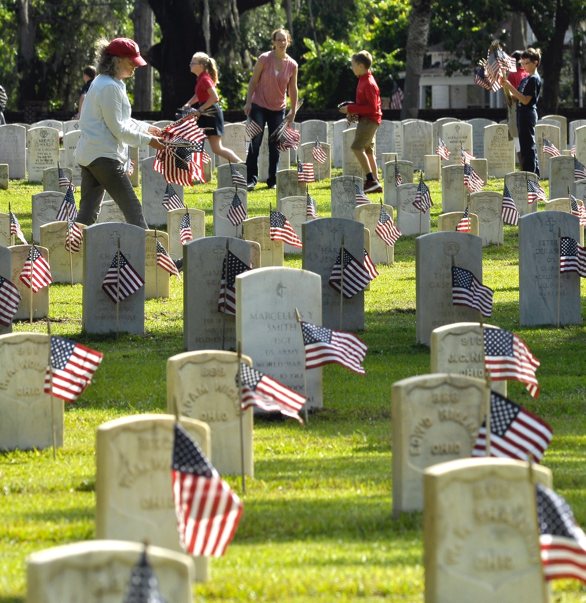 Barbara Pinto-Maurer, above, places American flags on some of the more than 19,000 head stones on May 25. Hundreds of area school children helped place flags on the more than 19,000 headstones in preparation for Monday's annual Memorial Day Ceremony. Photo by Bob Sofaly.