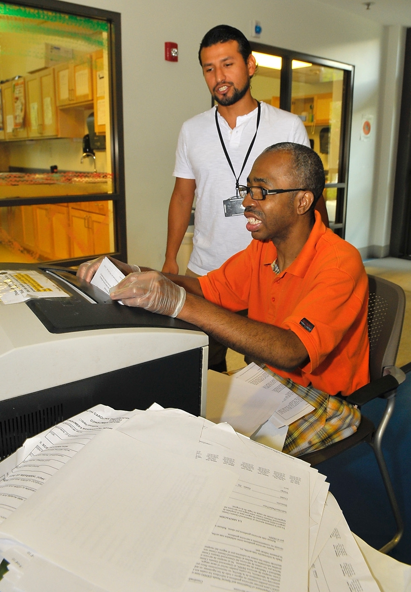 Bruce Marroquín stands over Bruce Shaw and makes sure he feeds documents into the shredder properly at the Beaufort County Department of Special Needs.