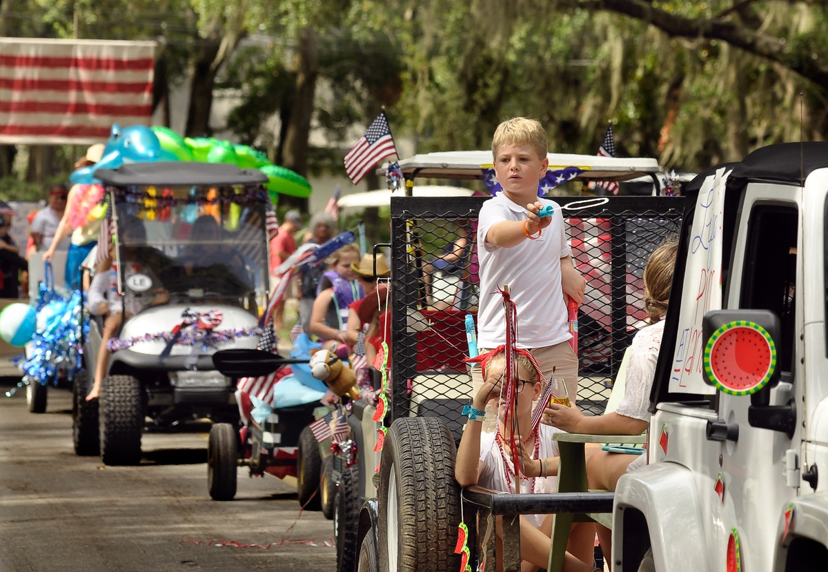 Gibson O'Neal, center, has some difficulty with his bubble wand during the annual Lands End Fourth of July parade on July 1 on St. Helena Island. Unable to get any serious bubbles generated, Gibson took to throwing candy to onlookers.