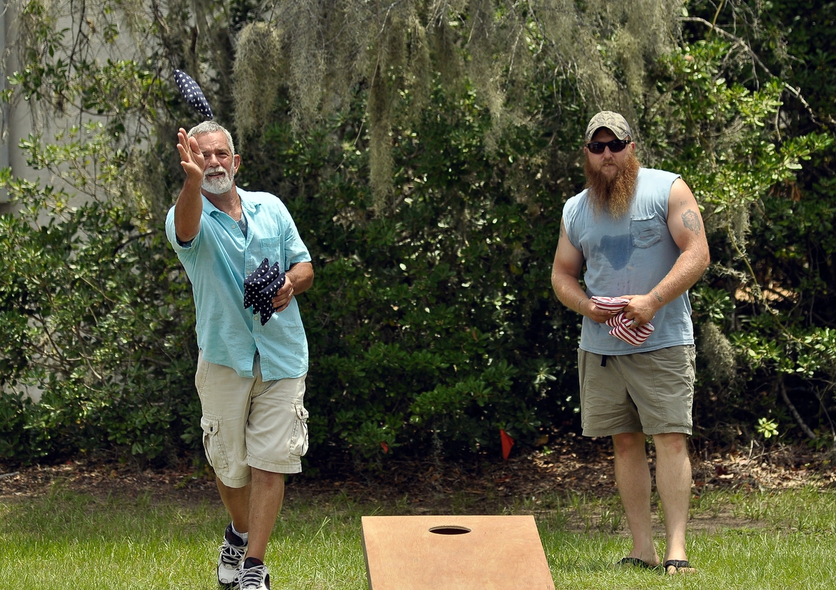 The Rev. Leon Meadows, pastor of Riverview Baptist Church, tosses one of his bags during a friendly game of cornhole. At left is Jeremy Todd.
