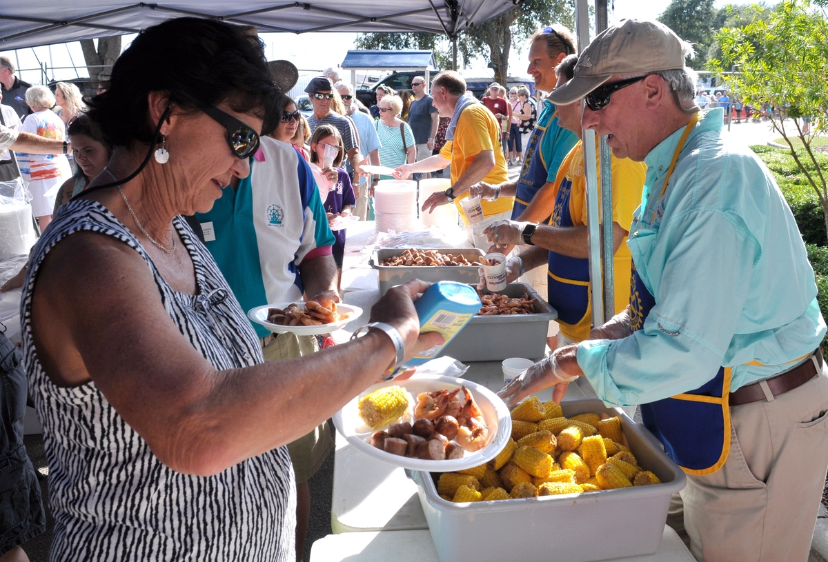 Marge Barber, left, squirts butter on her corn while volunteer Joe Lee, right, help her husband John during the annual Lowcountry Supper at Waterfront Park at the 2016 festival.