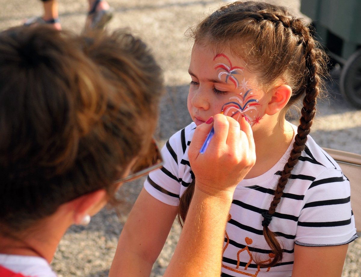 Sapphire Herreman, right, gets fireworks painted on her face by volunteer Megan Gartlan during the Fourth of July celebration at The Sands Beach in Port Royal.